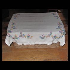 Gorgeous handmade embroidered table cloth from 1960s. There are clusters of beautifully embroidered flowers at all four corners. Pastel coloured straight stitch on linen type fabric. Measures 37 by 39 inches. Freshly laundered on cool wash and in excellent condition. Perfect for