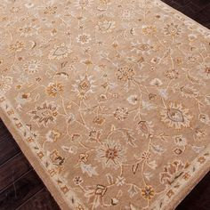 Hand-tufted wool rug with floral motif.  Product: RugConstruction Material: 100% WoolColor: Tan
