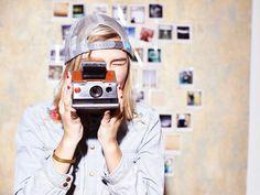 woman taking photos with polaroid camera