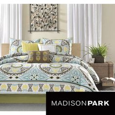 This cotton sateen set features dusty shades of green, teal, brown, and yellow and beautiful blue medallion motif that repeats across the comforter and is centered on each sham.
