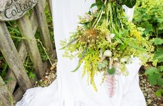 Wild English country garden bouquet freshly picked from the field, including echinops, solidago, pink astilbe, purple veronica and artichokes. Wedding flowers by London based Floral designers Okishima & Simmonds. www.okishimasimmonds.com
