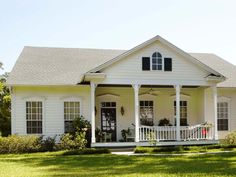 This cottage home boasts an inviting front porch with decorative pillar supports. An abundance of windows along the front allows for natural light to stream in, giving an open feel to this cozy home.