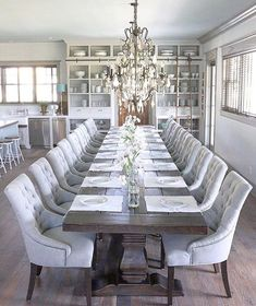 French dining room features a long plank dining table lined with ...