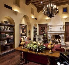 Tuscan design living room with so many details, the built ins, that stunning fireplace, the beamed ceiling and the chandelier and lets not forget the furnishings.....