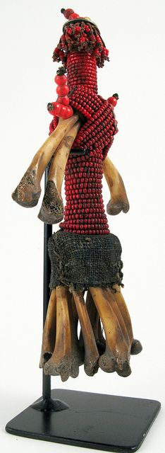 Africa |  Beaded Doll with bones, Fali/Namji, Cameroon. The body is adorned with beads, the skirt wraped with a fragment of hand loomed Ndop cloth.  The limbs are made from chicken bones.  The head is dressed with an old west African 1944 coin and the hair threads decorated with old 2mm white heart glass trade beads. | Image copyright, Ann Porteus, Sidewalk Tribal Gallery, via Flickr