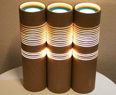 Paper Tube Lamp by Ruth Oh  Ruth Oh transforms everyday paper postage tubes into elegant cylindrical table lamps by simply slicing away sections of carboard. They're designed to use energy-efficient bulbs like LEDs or CFLs which run at cooler temperatures than incandescents.