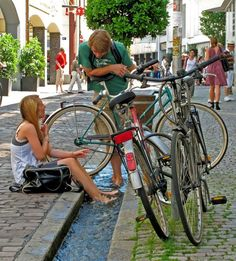Chilling at the rill on the Schusterstraße, Freiburg, Germany. Many streams run through the city, diverted from the central Dreisam River. Freiburg (pop 250,000) also has 400 km of bikeways.