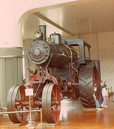 A giant steam tractor in Henry Ford Museum, in Dearborn, Michigan.   Compare the tractor's size with the children by the wheel.