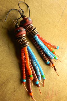 African trade beads on six strands of waxed linen cord in a tribal style tassel earring design. Red, orange brown and turquoise blue blend together with rings of copper and inlaid horn Mala beads atop the fringe. The Mala beads are vintage from Nepal with inlays of turquoise and coral that are complemented by the colors of the trade beads. The ear wires are copper ones that I have made myself, for a total length of 3.5 inches. With all these beads, there is a little bit of weight to these…