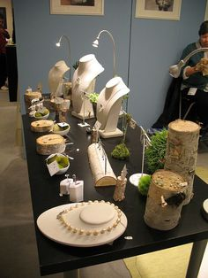 Display at OOAK by Moira K. Lime, via Flickr {Inspiring colors, love the touch of fresh green...and using tree stumps for jewelry display} #JewelryDisplays