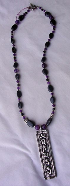 This necklace is made with beautiful glass and stone beads in the night colors of deep purple and black. The metal pendant is written in Sanskrit: Om Ma-ni Pad-me Hum - meditation mantra. These six syllables represent many things for Buddhists, one being six virtues: generosity, ethics, patience, diligence, renunciation and wisdom.