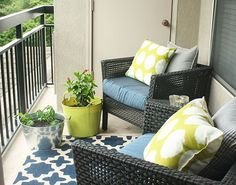 Don't kick these buckets--they're pretty, and besides, they're holding herbs on blogger Jewel Hazelton's small patio. How clever to match the colors of her container to her pillows, and echo the blue seat cushions with a rug! Click on for more small garden design tips! #smallPatioFurniture
