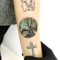 Miniature landscape circle tattoo on the inner forearm.