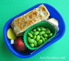 Contents of preschooler lunch: Rectangular Korean vegetarian dumplings (pan-fried mandu, like potstickers with a crispy bottom and soft steamed top) and dipping sauce, edamame, strawberry and a shelf-stable mini pudding cup