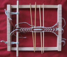 A weaving frame used as sprang loom. This frame comes with a shed stick, but it is a separate piece (not fastened to the frame), so that could just be left out. The work in progress is a traditional Finnish sprang ribbon in mirrored basic sprang; it is about 2-2.5 cm wide.