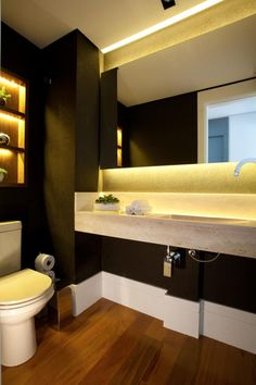 Lavabo rico em detalhes decoração. Tampo com cuba esculpida em mármore travertino e paredes com papel de parede de seda na cor berinjela inspiram o decor. Nicho embutido iluminado. Projeto de reforma e design de interiores em apartamento de 250m2.
