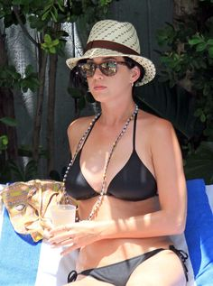 Katy Perry stuns in a classic black triangle top bikini. A long necklace is the perfect simple accessory! via StyleList
