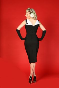 Sleeveless white-lined black Bettie Page wiggle dress, rear view. Square neck and back V with wide wings & decorative button closure; princess dart bodice with front triangular cutout at bust; removable accent belt at natural waist; fitted below-the-knee skirt with high rear vent; and back hidden zipper. Stretch bengaline, $140