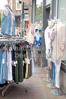 Paspoppen en kledingrek met hemdjes staan op de stoep voor de kledingwinkel