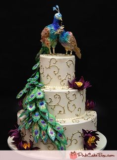 Intricate, elegant and gorgeous peacock and peahen and lotus flower themed wedding cake in a palette of purple, green, ivory, blue and gold.
