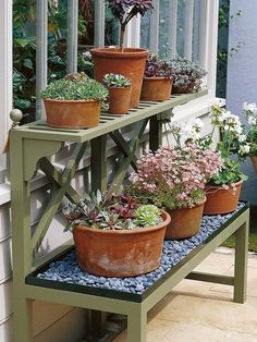 Gardening on a budget- create  garden benches for your pots of flowers - also love the rocks under the plants, maybe I could do that?