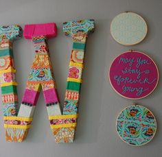 cardboard letter wrapped in fabric and ribbon & embroidery hoops filled with fun colored fabrics hung on the wall. Inexpensive way to add color to the walls!