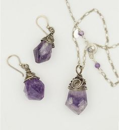 """Natural Amethyst Crystals """"in the rough"""" are wrapped in sterling silver filled wire a touch of patina and some graceful swirls.  The necklace is on silver plated chain with a secure but easy to operat"""