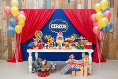 """A festa com tema circo, da Jazz Assessoria em Eventos (www.jazzassessoria.com.br), teve um painel com estrutura metálica atrás da mesa do bolo. Coberto com tecido azul """"bic"""", ele tinha, nas laterais, panos vermelhos para dar acabamento de cortina. Peças em MDF, a moldura amarela e a palavra """"Circus"""" foram costurados no centro do painel"""