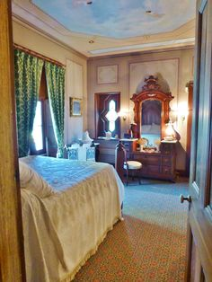 Entering the master bedroom at the Ebenezer Maxwell Mansion, you'll notice the handpainted ceiling with clouds and cherubs. The walls also feature handpainted panels. There's an imposing Renaissance Revival vanity across the room with wall-mounted sconces too.