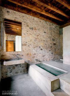 Refúgio do século 16 mescla aço corten e paredes de pedra