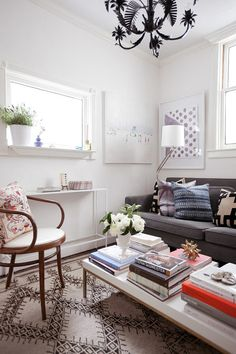 "When it comes to a small living area, sometimes more is, well, more. Jordan Ferney of Oh Happy Day used to live in an apartment that was 500 square feet, and called her living room ""essentially a small seating area."" Instead of keeping it bare, she did the opposite, decorating with her favorite books, paintings, and light fixtures. The result makes the space feel stylish and welcoming, despite the size."
