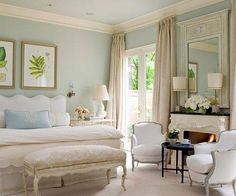 Blue walls, botanical print, tall beige curtains, comfy hotel-like bedding