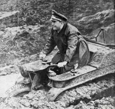 """Original caption: Albert Speer, Nazi Minister for Armament and Munitions is the pleased looking test pilot of this new German """"Tractorcycle"""" designed to make the Nazi way easier through the mud of Russia and Tunisia. the vehicle is so deeply mired here, that it is impossible to check, but apparently it runs on tractor treads. Germans claim it is a success."""