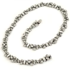 This vintage-style necklace features a fluid band of Art Deco inspired 'torch' links set with hundreds of clear crystal stones-rounds and baguettes.