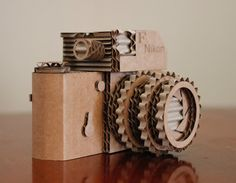 This handcrafted, laser-cut camera is approx 6.5 L x 4.5 H. It was lovingly crafted from 3/16 cardboard made from 40% recycled material. It is styled after my grandfathers 1960s era Nikon.