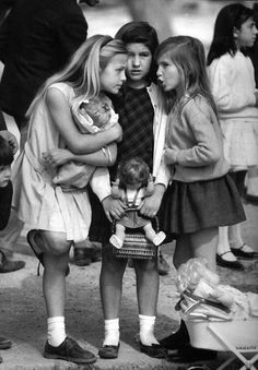 Girls with dolls whispering to each other. Date and location unknown.