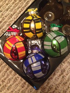 These glass ornaments are 3 inches by 3 inches.  This set includes Gryffindor, Slytherin, Ravenclaw, and Hufflepuff.  They are hand painted with