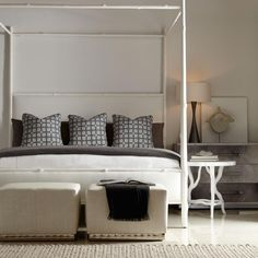 Luxury Bedroom with White Canopy Bed and Bedside Table, Twin Ottomans and White Bedding