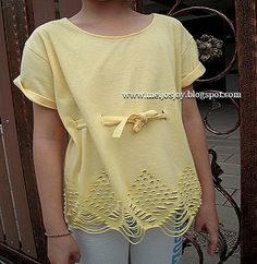 VERY QUICK  T-SHIRT MAKEOVER: tutorial shows how easy it is to cut a cool design into the bottom of the shirt.  The snips and strips create an eyelet effect.  Then thread a band of the fabric cut off the bottom through the waist to give it some shaping.