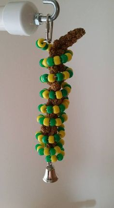 """Millet holder is made from stainless steel and beads.. This measures approx. 8"""" long and comes with a bell on the bottom. You can add millet or you can even use a carrot or other veggies and fruit! Wa"""
