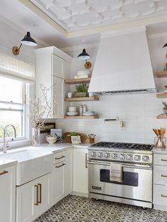 All-white kitchen with brass hardware and gray and white mosaic tile flooring.