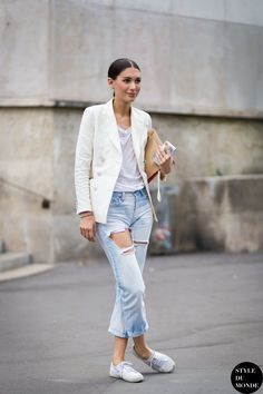 {White blazer and distressed denim.}
