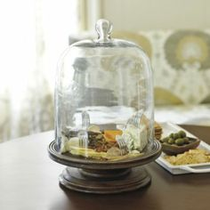 Display cheeses, keep baked goods fresh or cover a plant on the raised stand. Hand crafted of mango wood with heavy glass dome cover. Felt pads on bottom protect the surfaces of your table, buffet and countertops.Cloche on Wood Stand features: Indispensable for the frequent hostessFood-safe