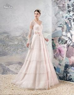 A light, airy dress of classical silhouette with thinnest lace border. The bodice is decorated delicate flowers and embroidered with strasses and beads. This model is offered with a detachable belt with decorative flowers.