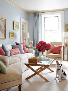 """Love the ceiling trim painted a different color as well!  """"In the living room, pale blue walls recall the color of the sky. The cream-color ceiling features an eggshell finish, which reflects light to make the room appear light and airy."""" The moldings slightly gold hue picked up gilded accents in room...punchy magenta add contrast to room's soft color palette - works with fireplace marble as well."""