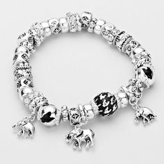 Silver tone stretch bracelet with elephant charms, silver beads, houndstooth beads and rhinestones.
