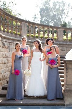 Bridesmaids in gray gowns with stunning hot pink bouquets. Brides is wearing Monique.
