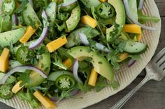 A Tropical Avocado Salad on a bed of arugula with mango, avocado, red onion, cucumbers and jalapenos.