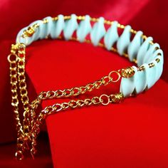 You'll make a dramatic entrance in this light blue and gold collar necklace. Or give it to your favorite edgy dresser. She's sure to adore this unique double memory wire collar composed of light blue German acrylic twist connectors and 4mm gold beads. The choker is finished with double gold chains and closed with two lobster clasps. It is 14 inches at its smallest point, tapering to a slightly larger size on the bottom for a flattering fit.  The Smallest Planet Guarantee All Smallest ...