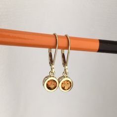 Filigree Citrine 14k yellow dangle earrings. Rich orange brilliant tones with minimalist feel, these sweet citrine gemstones can be worn with almost any outfit. I love their happy colors! Set with 5mm round .40 carats each, fair trade citrine gemstones in 14k yellow back set mountings on 14k yello